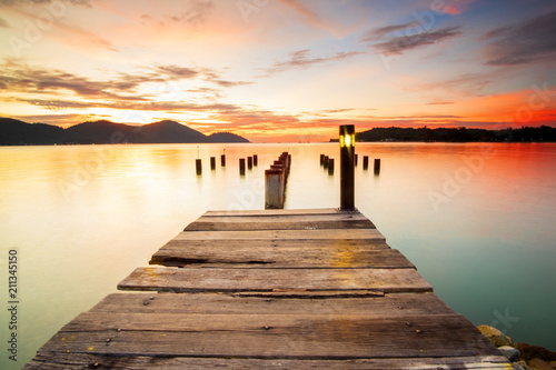 Plexiglas Pier Beautiful view of sunset at Marina Island Old Jetty,Malaysia. soft focus, blur due to long exposure. Visible noise due to high ISO.