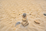 Balanced rocks are left on the beach in a zen type atmosphere - 211349787