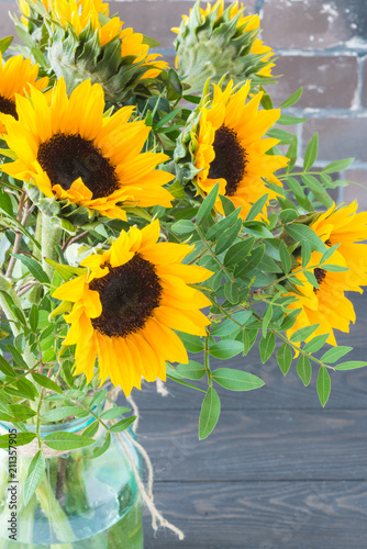 Bouquet of bright sunflowers in a glass jar on a wooden table.