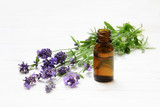 fresh lavender flowers and essential herbal oil in a brown glass bottle on white painted wood, copy space, close up - 211361516