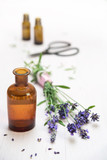 lavender flowers and bottles with essential herbal oil on white painted wood, copy space, vertical - 211361582