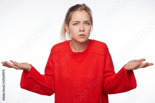 Leinwanddruck Bild Portrait of puzzled intelligent female student wears red oversized sweater, feels awkward, shrugs shoulders with hesitation, sees no way out, not knowing material on exam isolated on white wall.