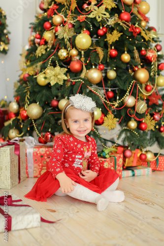 Young mother wearing white dress and keeping little female baby near Christmas tree. Concept of New Yea decoration and happy parent.