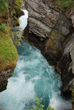 A pure blue river flows with a rapid flow between the rocky banks