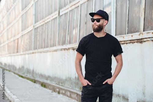Hipster przystojny mężczyzna model z brodą sobie czarny t-shirt puste z miejscem na logo lub projekt w stylu casual miejskich