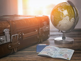 Travel or turism concept.  Old  suitcase  with open passport with visa stamps and globe. - 211379773