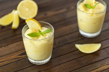 Fresh lemon citrus sorbet garnished with mint alongside. Lemon Frozen Granita Slush Drink.