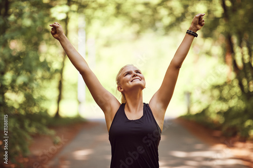 Smiling woman raising her arms in victory after a run - 211388115