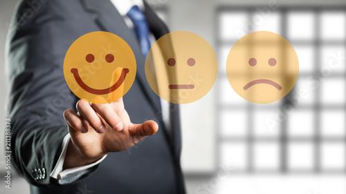 Geschäftsmann wählt lächelnden Smiley vor Bürohintergrund - 211388373
