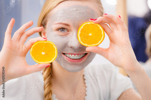 Happy young woman having face mask holding kiwi - 211395549