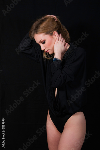 Sexy lady with glamour makeup and long blonde hair in body posing in studio, dark background. Elegant woman wearing black sensual lingerie. Erotic noir concept.  - 211399901