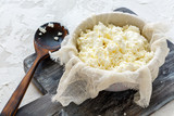 Fresh cottage cheese in a bowl and cheesecloth. - 211402117