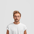 Vertical shot of puzzled European male with curly haircut, purses lips and looks in bewilderment, surprised to see big sales, dressed in casual white t shirt, isolated over studio background