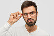 Leinwanddruck Bild - Headshot of angry unshaven male looks seriously at camera, frowns face, touches rim of glasses, sees in bewilderment, isolated over white background. Photo of annoyed boss stares through spectacles