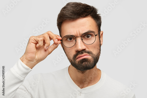 Leinwanddruck Bild Headshot of angry unshaven male looks seriously at camera, frowns face, touches rim of glasses, sees in bewilderment, isolated over white background. Photo of annoyed boss stares through spectacles