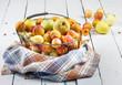Leinwanddruck Bild - Ripe tasty fresh apricots and apples in  woven metal basket