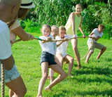 Kids with moms and dads playing tug of war - 211421736