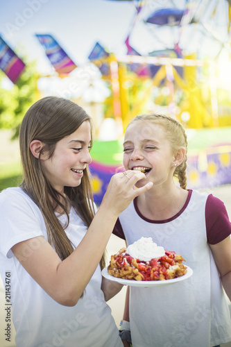Fotobehang Amusementspark Two laughing and smiling teenage girls eating a funnel cake at an outdoor carnival or amusement park. Cute expression in this candid photo