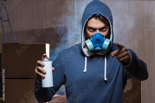 Graffiti painter in dark smokey room - 211437366