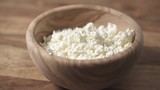 closeup cottage cheese falling into wood bowl - 211463194