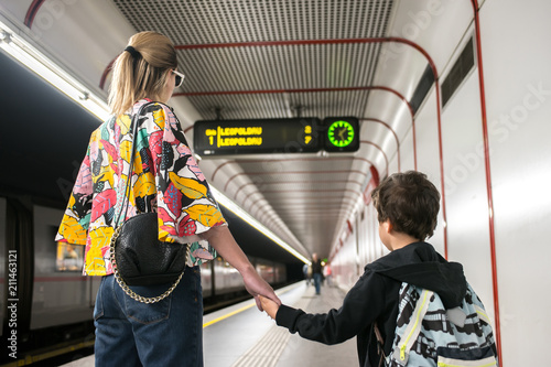 Woman with kid waiting train at the station