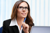 Thinking businesswoman working with laptop - 211466153
