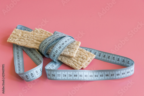 the loaves and the tape diet slim health on a pink background. slimming loaves. close up - 211469995