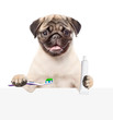 Leinwanddruck Bild - Pug puppy with a toothbrush and a tube of toothpaste above white banner. isolated on white background