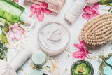 Skin cream with flowers petals and others body care cosmetic products and accessories on white background, top view - 211477183