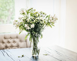 Summer flowers bunch in vase on table at window in living room with falling petals. Cozy home and house decoration - 211479178