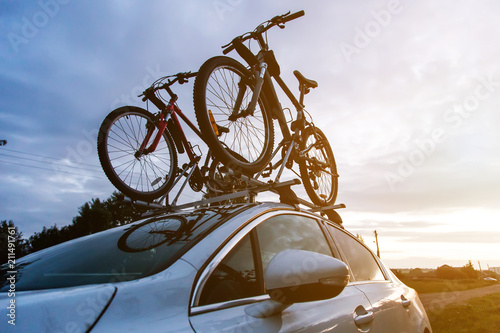 Leinwanddruck Bild Bike transportation - two bikes on the roof of a car against a beautiful sky. the end of the transportation of large loads and travel by car