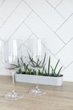 Wineglasses stacked on a wooden table against white background. - 211494392