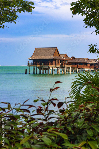 Wooden cottages, bungalows on clear blue water waiting for tourists in tropical oceans - 211494785