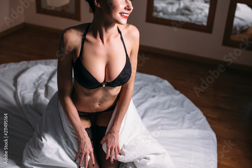 Luxury brunette model with natural big bubs in bra sitting on the bed - 211495164