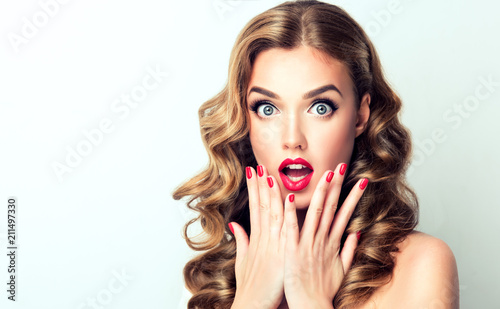Leinwanddruck Bild Woman surprise showing product .Beautiful girl  with curly hair  pointing to the side . Presenting your product. Isolated on white background. Expressive facial expressions