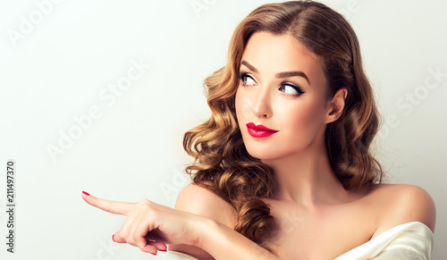 Woman surprise showing product .Beautiful girl  with curly hair  pointing to the side . Presenting your product. Isolated on white background. Expressive facial expressions