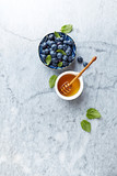 Fresh Blueberries with Honey and Mint Leaves on gray marble background. Flat lay. Healthy Diet Concept. Copy space - 211497513