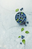 Fresh ripe blueberries with mint leaves in a bowl on gray marble background. Flat lay. Copy space. - 211497529