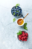 Fresh Blueberries and Raspberries with Honey and Mint Leaves on gray marble background. Flat lay. Healthy Diet Concept. Copy space - 211497536