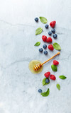Fresh Blueberries and Raspberries with Honey and Mint Leaves on gray marble background. Flat lay. Healthy Diet Concept. Copy space. - 211497554