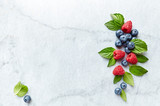 An Arrangement of fresh raspberries, blueberries  and mint leaves on gray marble background. Flat lay. Healthy diet concept. - 211497561
