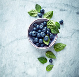 Fresh ripe blueberries with mint leaves in a bowl on gray marble background. Flat lay. Copy space. - 211497569