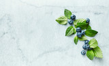 An arrangement of  blueberries with mint leaves on gray marble background. Flat lay. Copy space. - 211497572