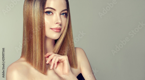 Beautiful model girl with shiny brown and straight long  hair .Keratin  straightening .Treatment, care and spa procedures.Medium length hairstyle. Coloring, ombre,and highlighting