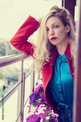 Outdoor fashion portrait of glamour young cheerful stylish lady wearing trendy red coat. Blonde long hair. Full lips, green eyes.