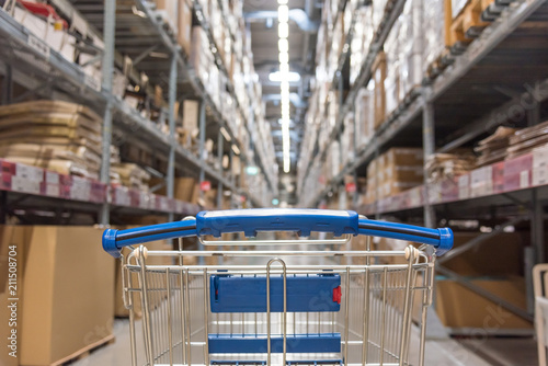 Warehouse storage of retail merchandise shop. Trolley Shopping Cart Between Dry Grocery Shelf Section in Supermarket Warehouse Retail Outlet as Shopping Concept.