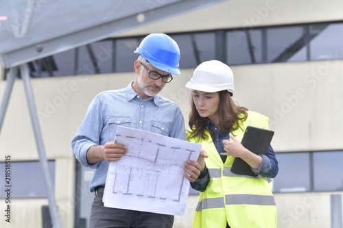 Construction engineers meeting outside building - 211518515