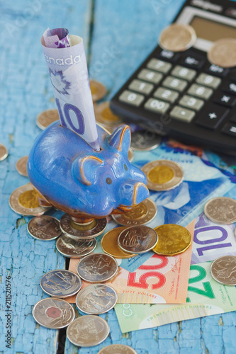 Canadian dollars, coins, piggy bank and calculator on the wooden background - 211520576