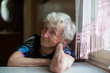 An elderly woman sits thoughtfully at the table.
