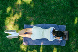 young adult woman laying with laptop in city park on green grass